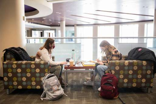 Freshmen Sam Lang, left, and Alivia Riemenapp tackle school work in the Anderson Student Center. Liam James Doyle/University of St. Thomas