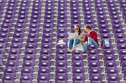 Roommates Katie Stambrosky, left, and Leanna Frisbie work together while enjoying the mild weather from the stands of O'Shaughnessy Stadium. Liam James Doyle/University of St. Thomas