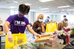 Students Roman Adhikari and Ayan Ahmed work to organize and fill bags of food items in Opus Hall where Tommie Shelf expanded it's efforts to the Minneapolis campus. Liam James Doyle/University of St. Thomas