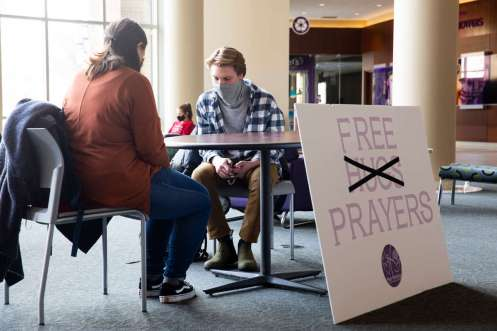 Francesco Scarchilli prays for friend Emily Kane (visiting campus) while offering free prayers as part of a Peer Ministry program in the Anderson Student Center. Mark Brown/University of St. Thomas