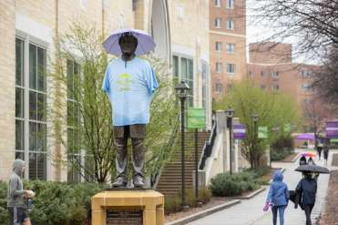 The statue of John Ireland is dressed in a t-shirt and an umbrella hat during the Spring into Spring event hosted by Student Affairs.