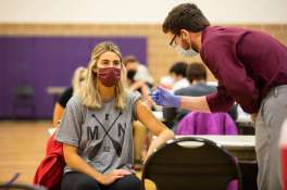 Korbyn Perpich receives the COVID-19 vaccine in the McCarthy Gym. Liam James Doyle/University of St. Thomas