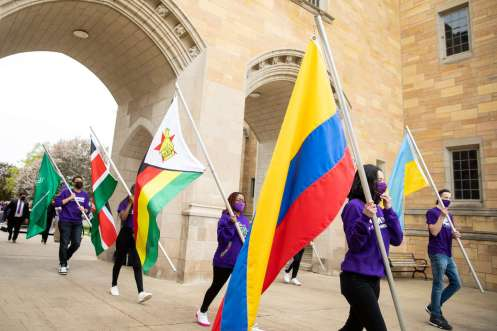 International Freshman students carry their respective country's flags.