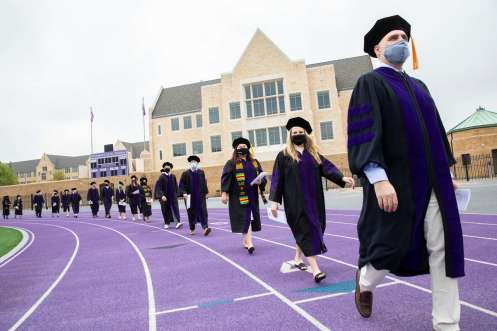 Students from the School of Law's Class of 2020 walk into O'Shaughnessy Stadium. Liam James Doyle/University of St. Thomas