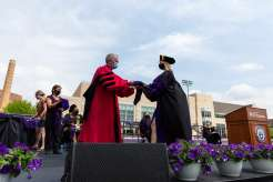 Dean Robert Vischer hands out hoods on stage during the School of Law Class of 2021 Commencement Ceremony. Mark Brown/University of St. Thomas