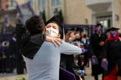 A student embraces their family following the Dougherty Family College commencement ceremony. Liam James Doyle/University of St. Thomas