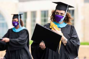 Students receive their diplomas during the graduate commencement ceremony. Liam James Doyle/University of St. Thomas
