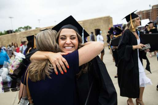A student receives a hug after the commencement ceremony for graduate programs. Mark Brown/University of St. Thomas