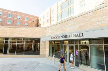 Students pass by Tommie North Residence Hall during a sunny evening. Liam James Doyle/University of St. Thomas