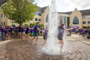 Students celebrate by running through the water fountain on Monahan Plaza. Mark Brown/University of St. Thomas
