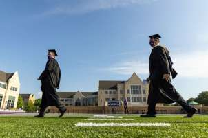 Students walk toward the stage during the commencement ceremony for graduate program. Mark Brown/University of St. Thomas