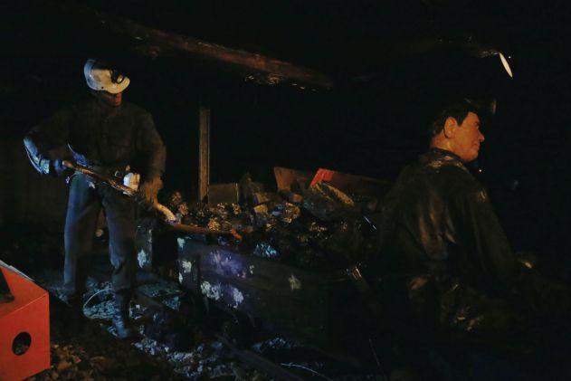Miners shoveling coal into rail car.