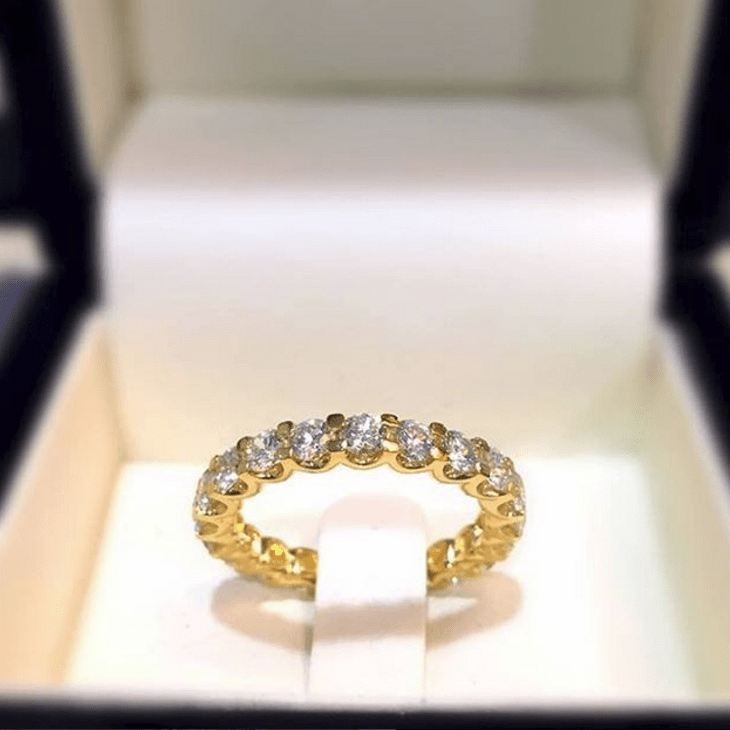 Chloe diamond eternity ring with round diamonds in claw setting in yellow 18K gold