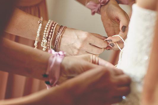 Bridesmaids tying up a bride's wedding dress