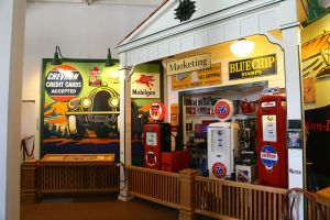 Display of oil company marketing with panels, gas station pumps, and other memorabilia.