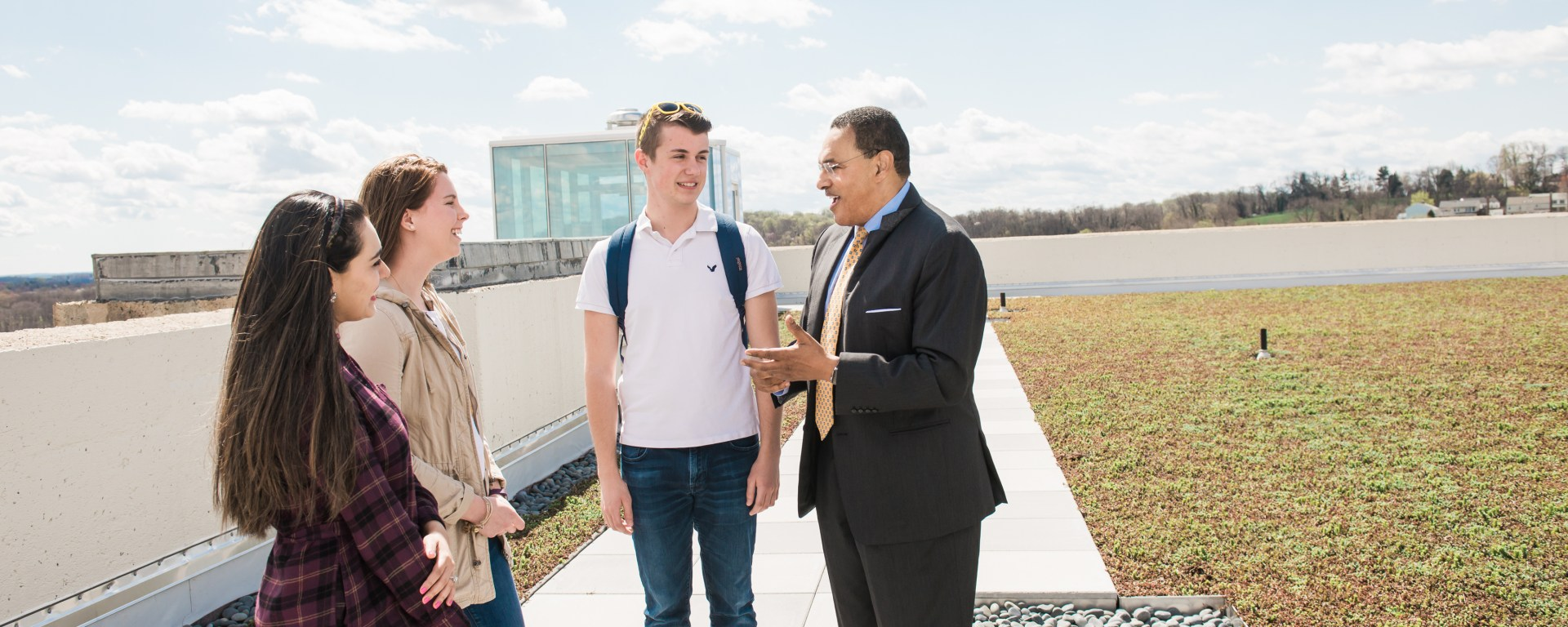 Man in suit stands with three students in casual clothes on a green roof with blue sky above.