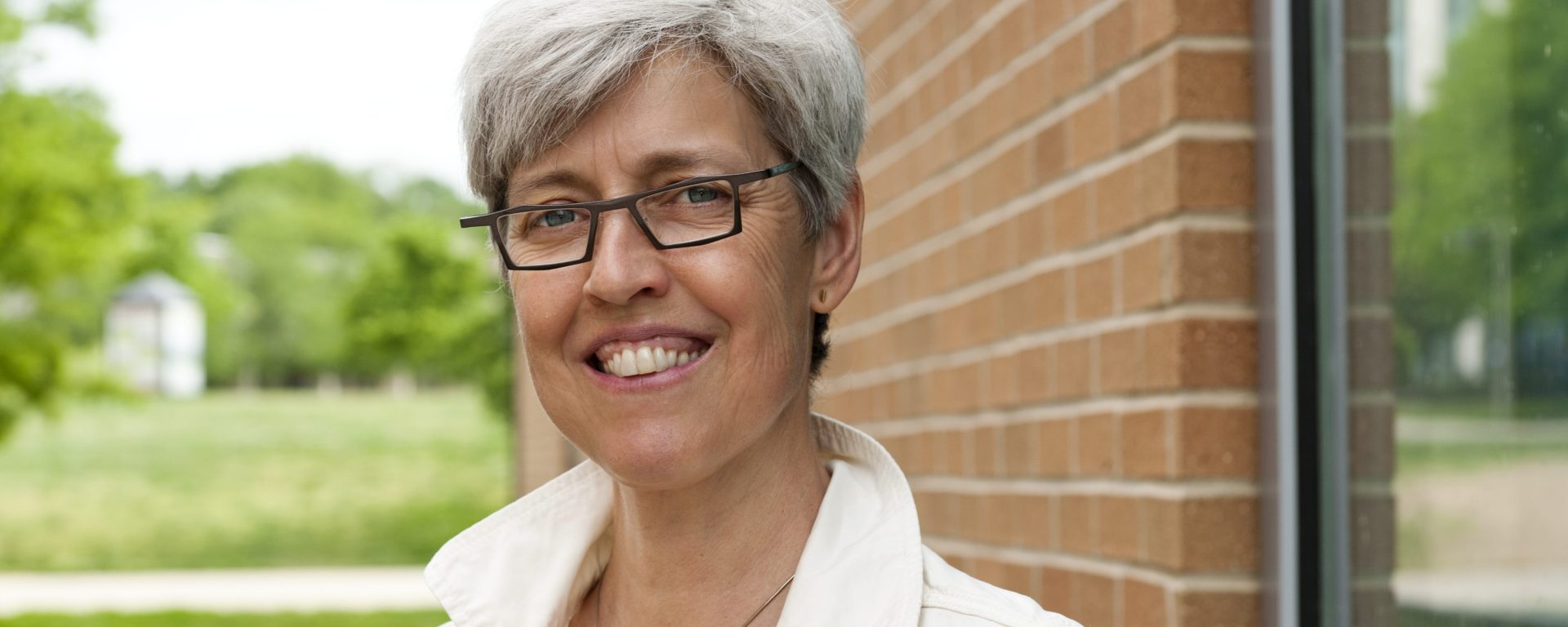 A woman with short grey hair with dark rimmed glasses and wearing a white dress shirt smiles at the camera. A red brick building and a small green tree is behind her.