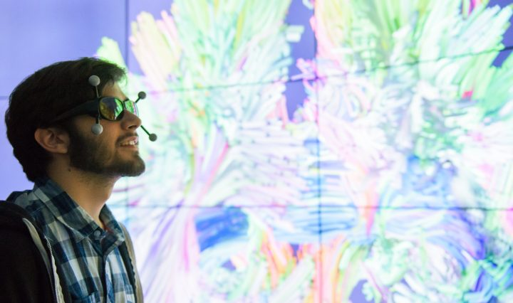 Young man wears VR glasses, standing in front of a glowing wall.