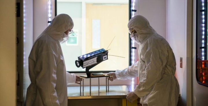 Two scientists in protective suits stand next to a piece of equipment with a large lens