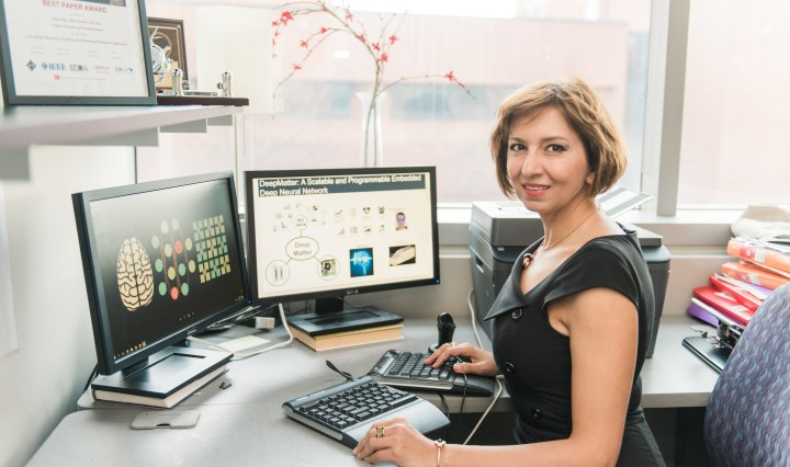 Middle-aged woman with short auburn hair sits in front of a computer. She wears of professional attire. A building and flours can be seen through the window in the background.