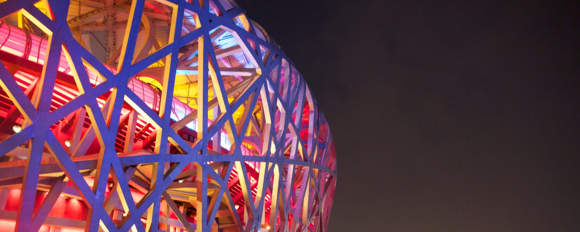 Photo of Beijing Olympic site, featuring metalwork in the shape of a web, with pink, orange, and yellow lights.