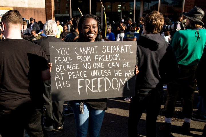 """Protester holds sign that reads, """"You cannot separate peace from freedom...because no one can be at peace unless he has his freedom."""""""