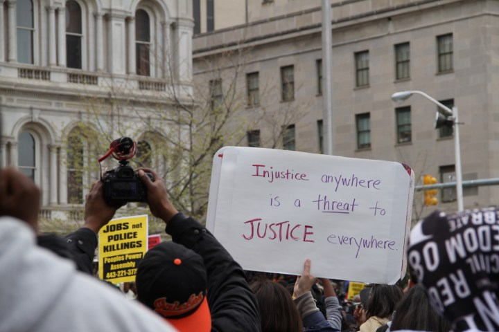 """Protester holds a sign reading, """"Injustice anywhere is a threat to justice everywhere."""""""