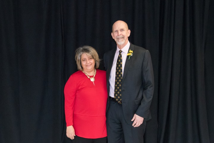 Woman in red shirt and man in suit with black and gold tie pose together.