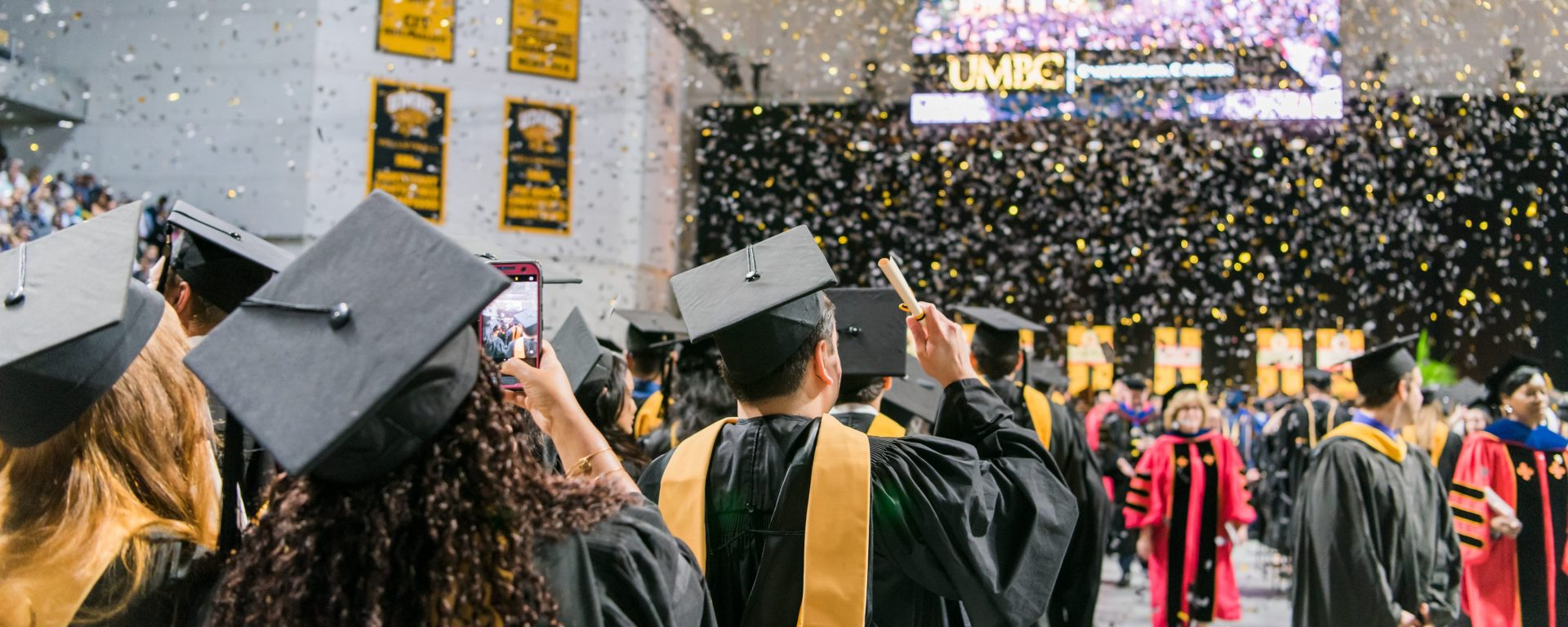 Graduates in black and gold caps and gold celebrate UMBC's spring 2018 graduate school commencement