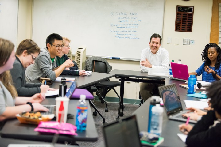 Teacher and a several students sit around tables set in the shape of a circle, eating snacks, typing on laptops, talking and smiling.