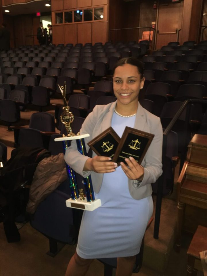 Young woman with dark hair wearing a grey blazer and a light blue dress smiles at camera while holding two plaques and one trophy while standing in an auditorium.