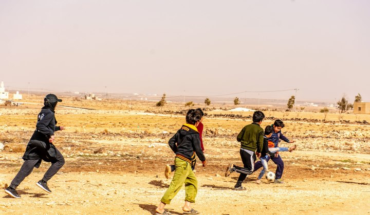 Maheen playing soccer with Syrian children in a Jordanian refugee camp after passing out soccer jerseys she helped fundraise for.