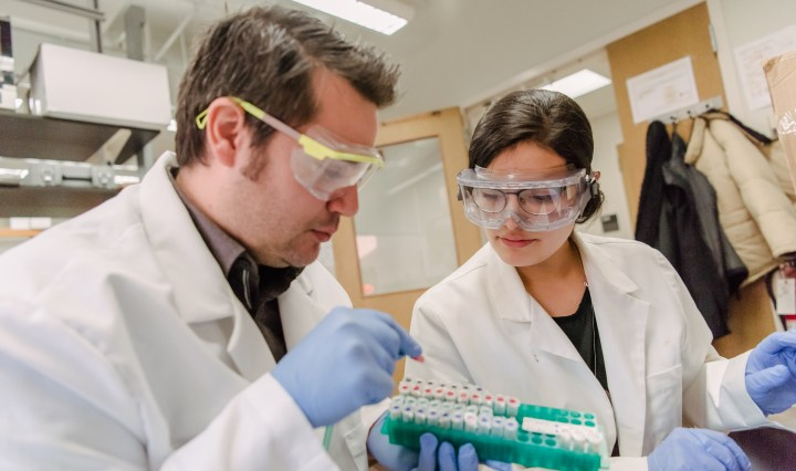 A man and woman wearing lab coats and goggles work in a lab, inspecting samples.