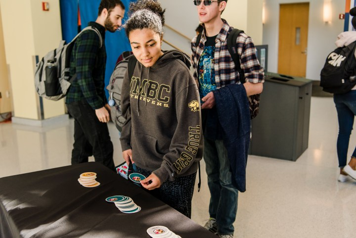 Students check out the new logo and grab stickers at campus event.