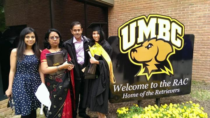A student in graduation clothing poses with parents and sister by UMBC sign.