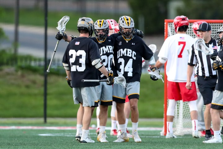 A group of UMBC men's lacrosse players in black, gold, and gray uniforms embraces each other on a field.