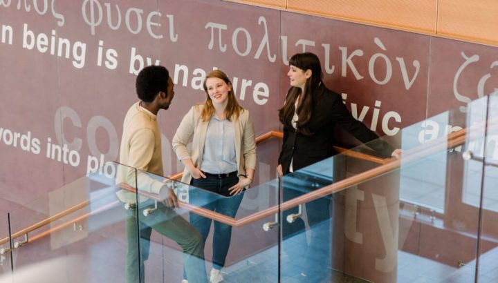 Students and faculty connect in UMBC's public policy building, in front of meaningful quotes in several languages.