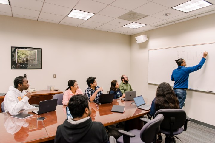 A student writes on a white board. Seven colleagues watch from their seats around a conference table.