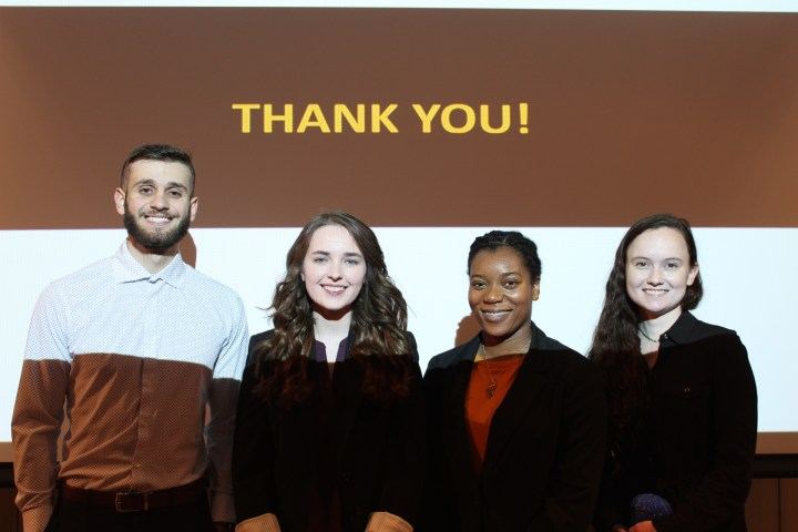 """Four students standing in front of """"thank you"""" screen."""