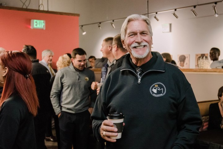 Man with white hair and a beard poses, smiling, holding coffee, wearing an OCA Mocha sweater, amidst a crowd.