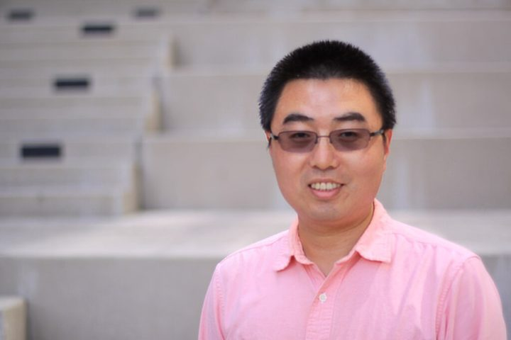 Headshot, man in pink shirt and glasses