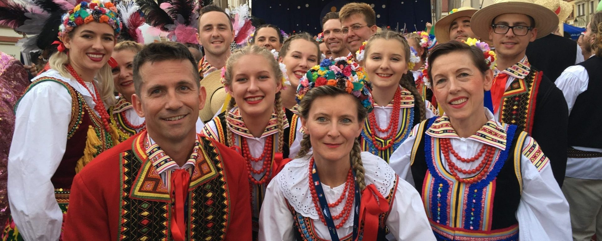 Large group of men and women dressed in traditional Polish clothing standing together at an outdoor Polish folk festival in Poland.