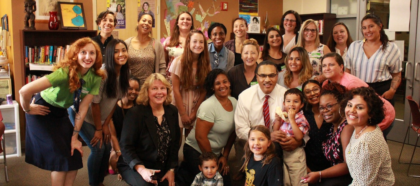 A diverse group of two dozen women poses in an informal cluster, along with a man in a tie and three children