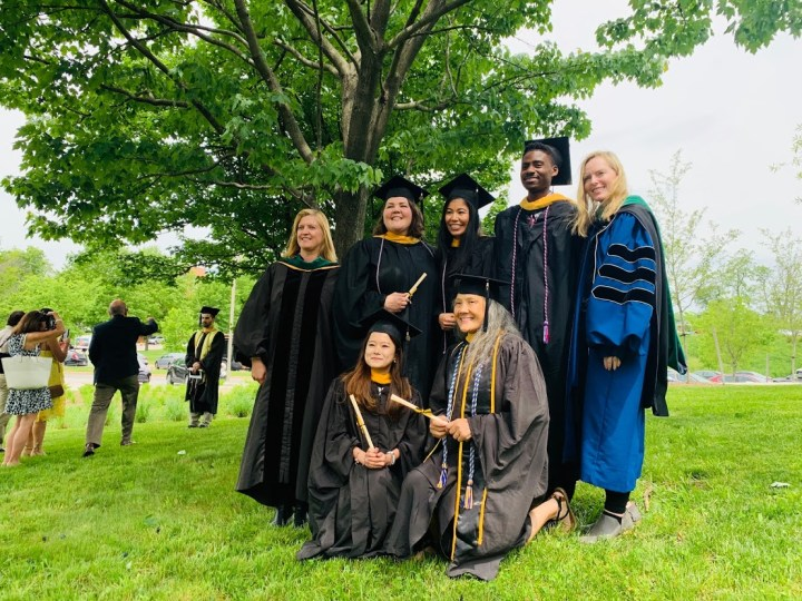 A group of five graduate students and two professors wearing caps and gowns standing under a tall tree in springtime.