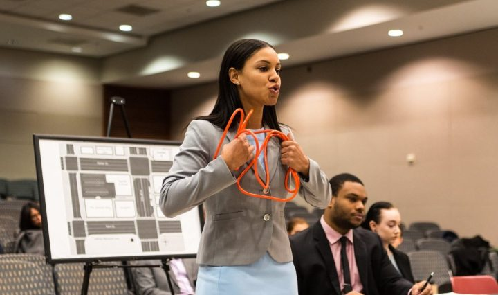 Young woman with long dark hair wearing a grey blazer and light blue skirt, standing and holding twisted orange wire,