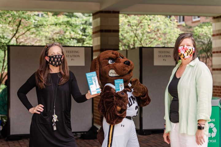 Two women stand on either side of a person dressed in a dog mascot costume. The women wear face masks. One holds up a thermometer in a package.