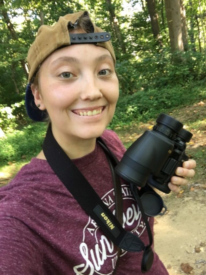 Student outdoors carrying binoculars