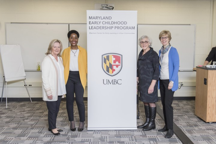 "A group of four women stand with a standup banner in between them. The banner reads ""Maryland Early Childhood Leadership Program"" and ""UMBC."" There is a wall of white boards mounted on the wall behind them and a large white paper pad on an easel."
