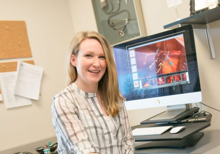 Portrait of smiling woman sitting in front of computer that features medical device imagery.