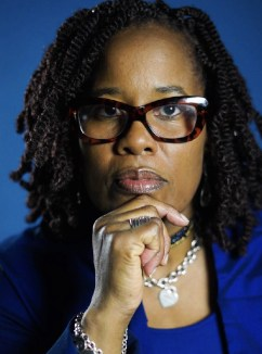 A Black woman with curly black hair wearing dark rimmed glasses and a cobalt blue suit looks straight at the camera holding her hand up to her chin.